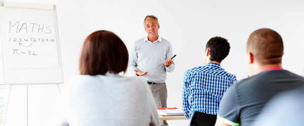 confident mature teacher giving presentation to students in school classroom